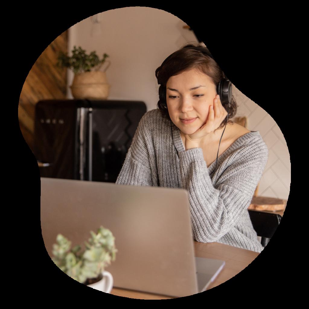 Kobieta patrzy w komputer oglądajac autentyczne wideo pomagające nauczyć się jej języka angielskiego.