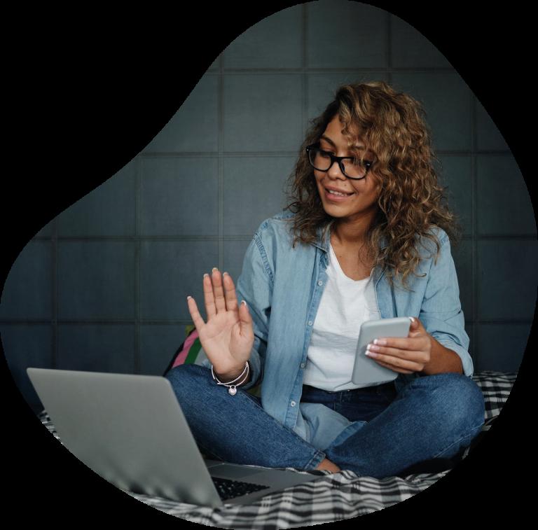 Kobieta rozmawia z komputerem ucząc się języka angielskiego online z domu.